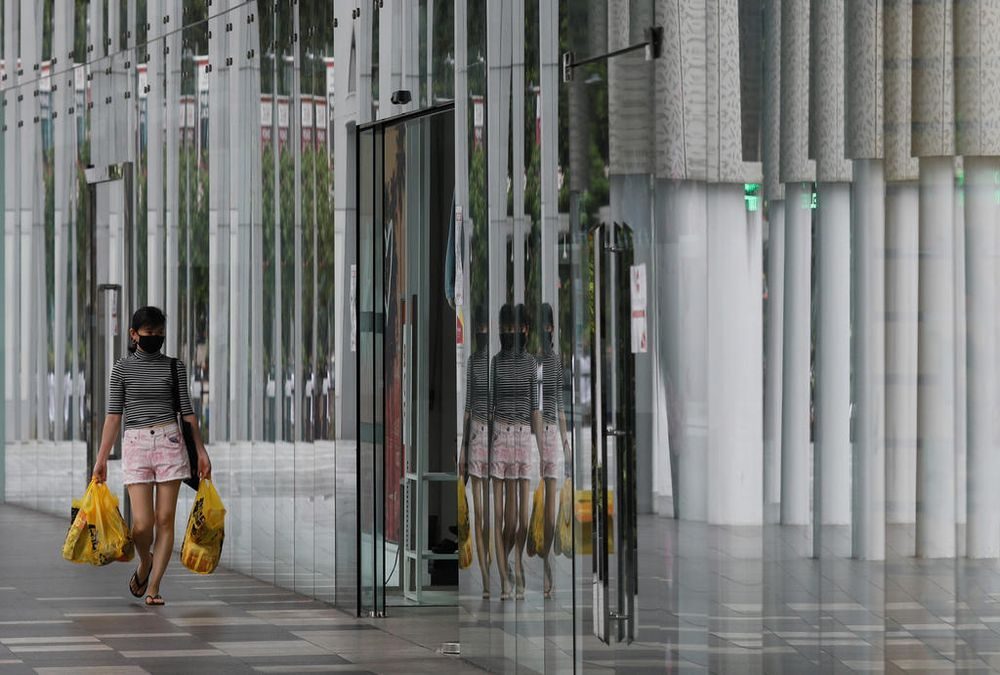 A woman wearing a protective face mask walks into a mall in Singapore. — TODAY file pic