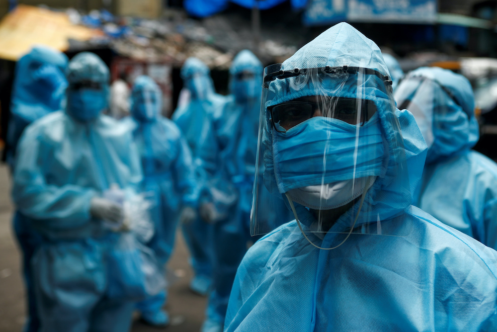 Healthcare workers wait to take off their personal protective equipment (PPE) after the end of a check-up camp for the coronavirus disease (Covid-19) at a slum in Mumbai, India June 14, 2020. — Reuters pic