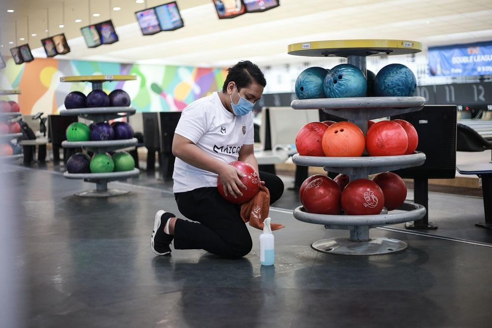 An employee disinfects bowling balls at Wangsa Bowl, a bowling centre located at Wangsa Walk Mall, in Kuala Lumpur June 9, 2020. — Picture by Ahmad Zamzahuri