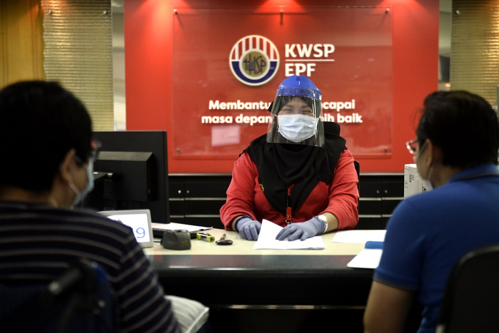 A staff member wears protective gear as she works at the Employees Provident Fund's headquarters in Kuala Lumpur. — Picture by Miera Zulyana
