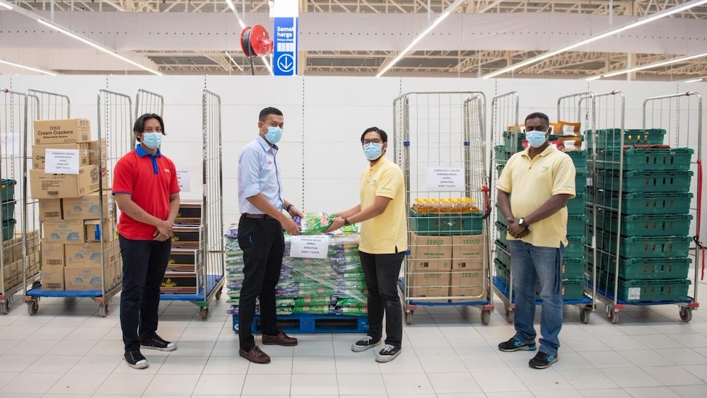 Tesco staff hand over the donated food items to Food Aid representatives. — Picture courtesy of Tesco Malaysia.