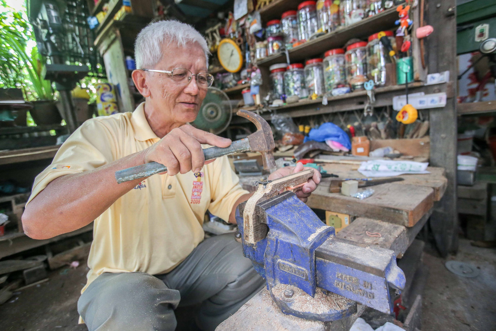 Retired headmaster Wee Ong Chin's home at Sitiawan doubles up as his workshop where he prepares toys and souvenirs to be given out when he performs at charity events. — Picture by Farhan Najib