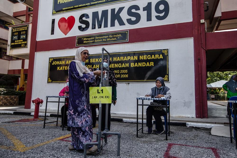 A teacher demonstrates the proper use of a foot pedal-operated hand sanitiser station Sekolah Menengah Kebangsaan (SMK) Seksyen 19 in Shah Alam June 23, 2020. — Picture by Firdaus Latif