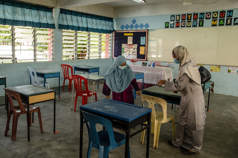 Teachers are seen arranging tables at a classroom in accordance to social distancing rules at the Sekolah Menengah Kebangsaan (SMK) Seksyen 19 in Shah Alam June 23, 2020. The Sabah Education Department has ordered 30 schools in Silam and Silabukan in Lahad Datu to close temporarily starting tomorrow until further notice. — Picture by Firdaus Latif
