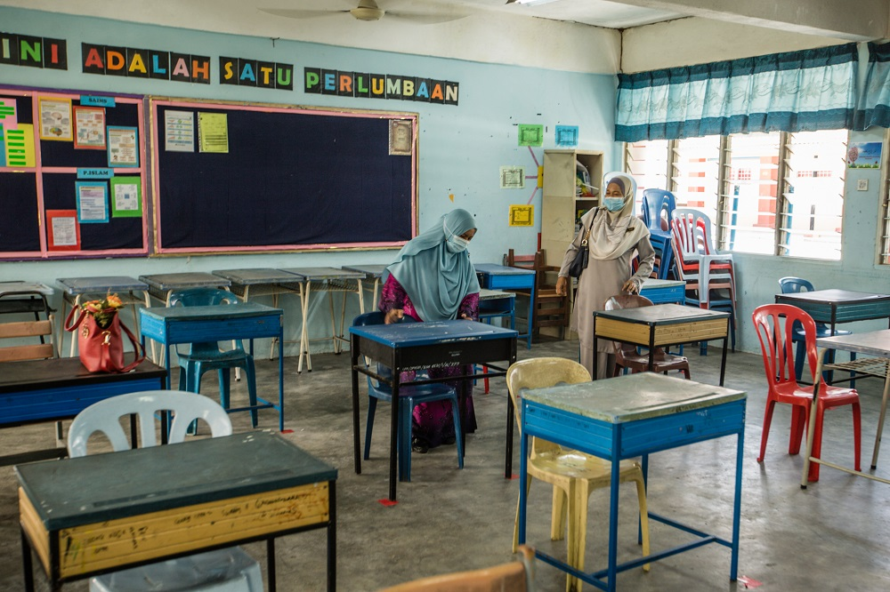 Teachers are seen arranging tables at a classroom in accordance to social distancing rules at the Sekolah Menengah Kebangsaan (SMK) Seksyen 19 in Shah Alam June 23, 2020. — Picture by Firdaus Latif