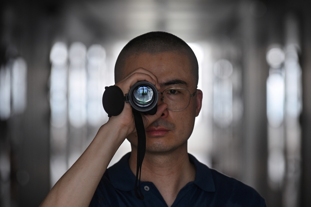 Dai Pengjun, a private detective who investigates suspected infidelities, posing with a prismatic scope he uses for work in Shanghai. — AFP pic