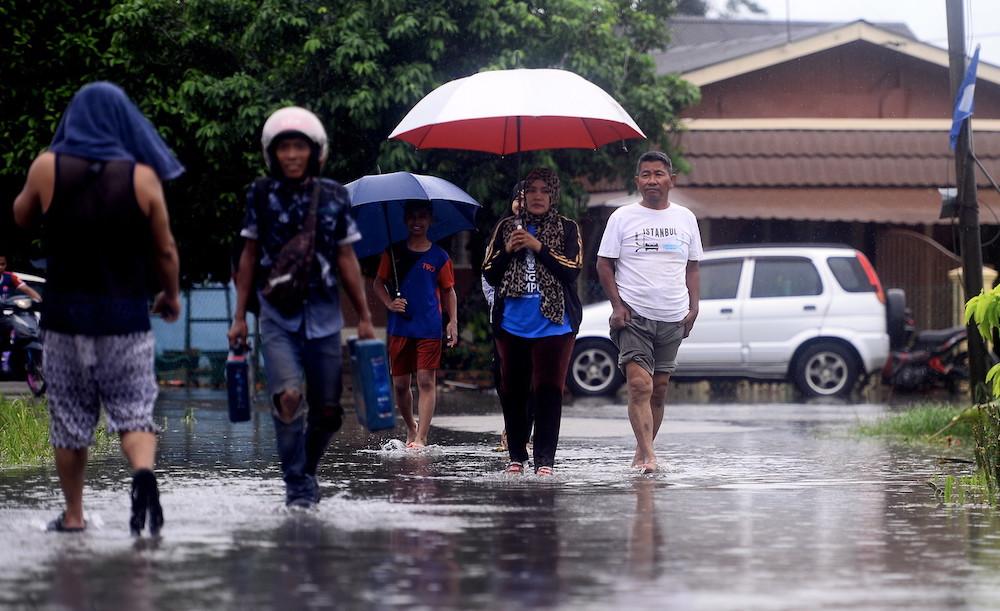 Residents of Kampung Parit Pasir Baru in the Pekan Nenas Pontian area wade through flood waters, June 20, 2020. — Bernama pic