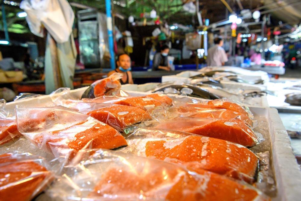 A vendor sells salmon at Khlong Toei Market, the biggest fresh market in Bangkok. — AFP pic