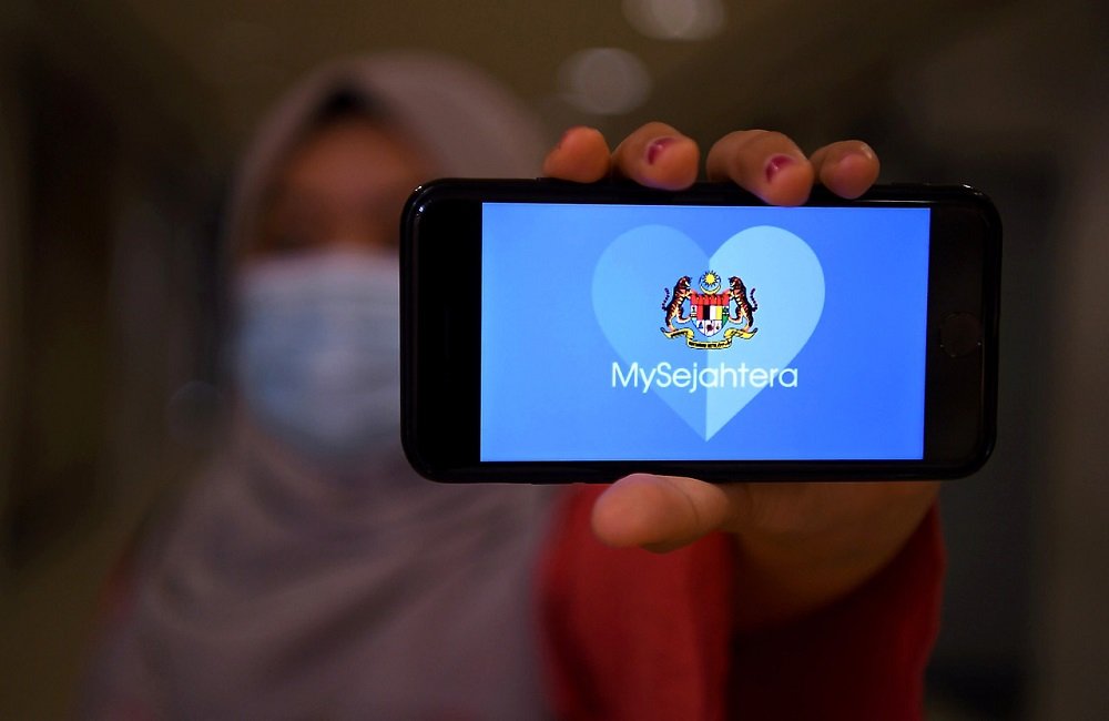 A woman holds up a phone displaying the MySejahtera app in Kuala Lumpur May 6, 2020. — Bernama pic
