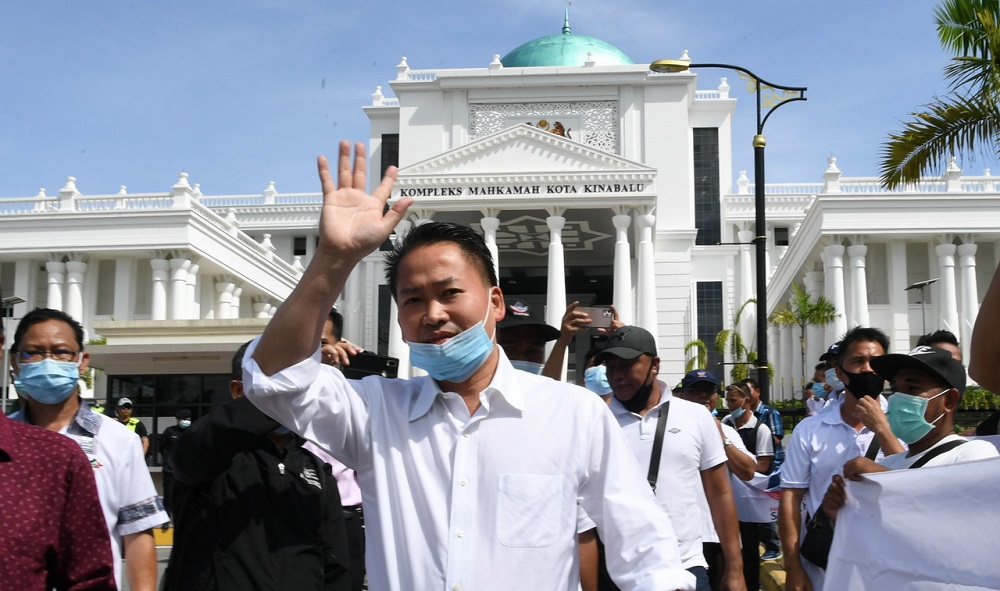 Datuk Peter Anthony waves at supporters as he leaves the Special Corruption Court in Kota Kinabalu June 18, 2020. — Bernama pic