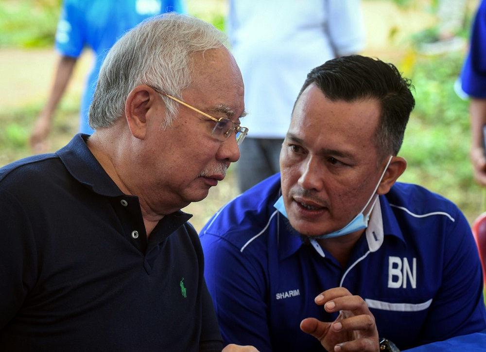Datuk Seri Najib Razak (left) and Barisan Nasional's candidate for the Chini by-election Mohd Sharim Md Zain are seen chatting during a visit the the Jakun Orang Asli settlement near Pekan June 25, 2020. — Bernama pic