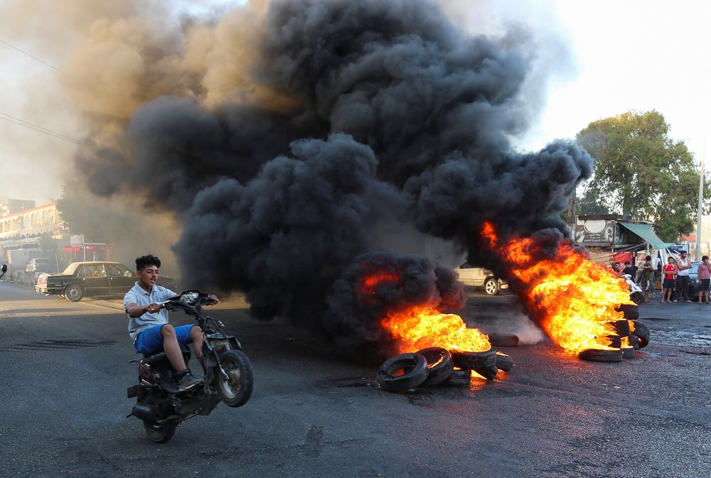 A youth man boy rides his motorbike near burning tires during a sit-in protest against the fall in pound currency and mounting economic hardship, in Ghazieh, Lebanon June 12, 2020. — Reuters pic