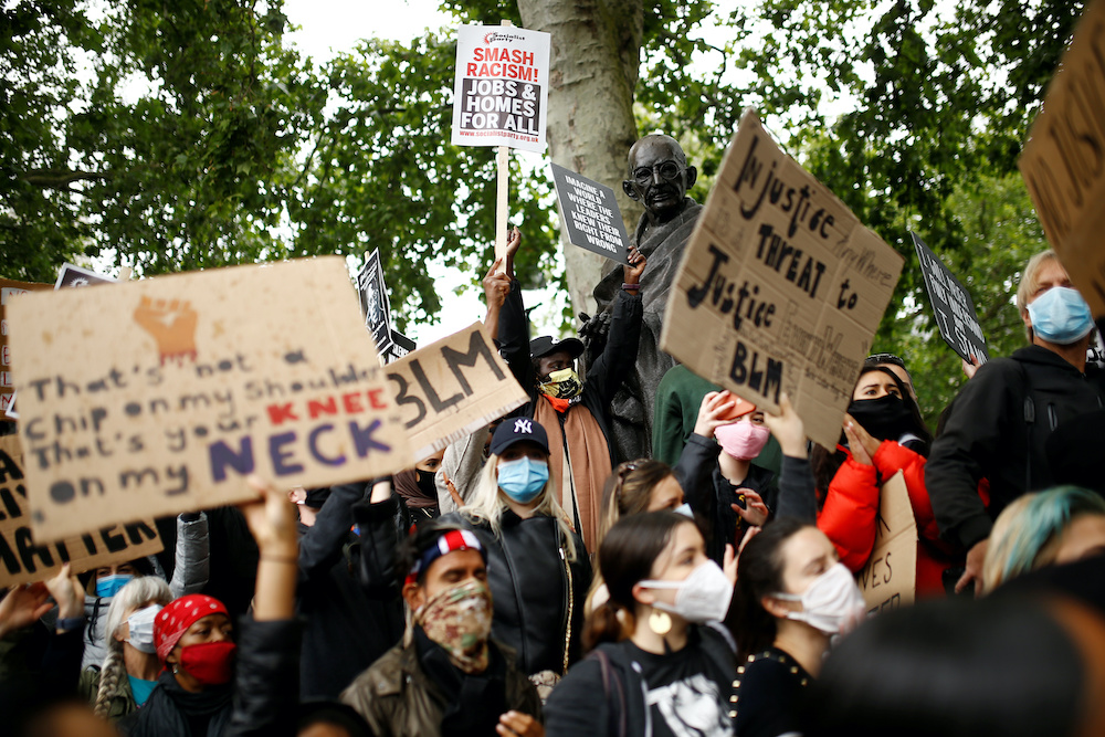 Demonstrators wearing protective face masks and face coverings hold placards during a Black Lives Matter protest in Parliament Square, following the death of George Floyd who died in police custody in Minneapolis, London, Britain, June 6, 2020. — Reuter