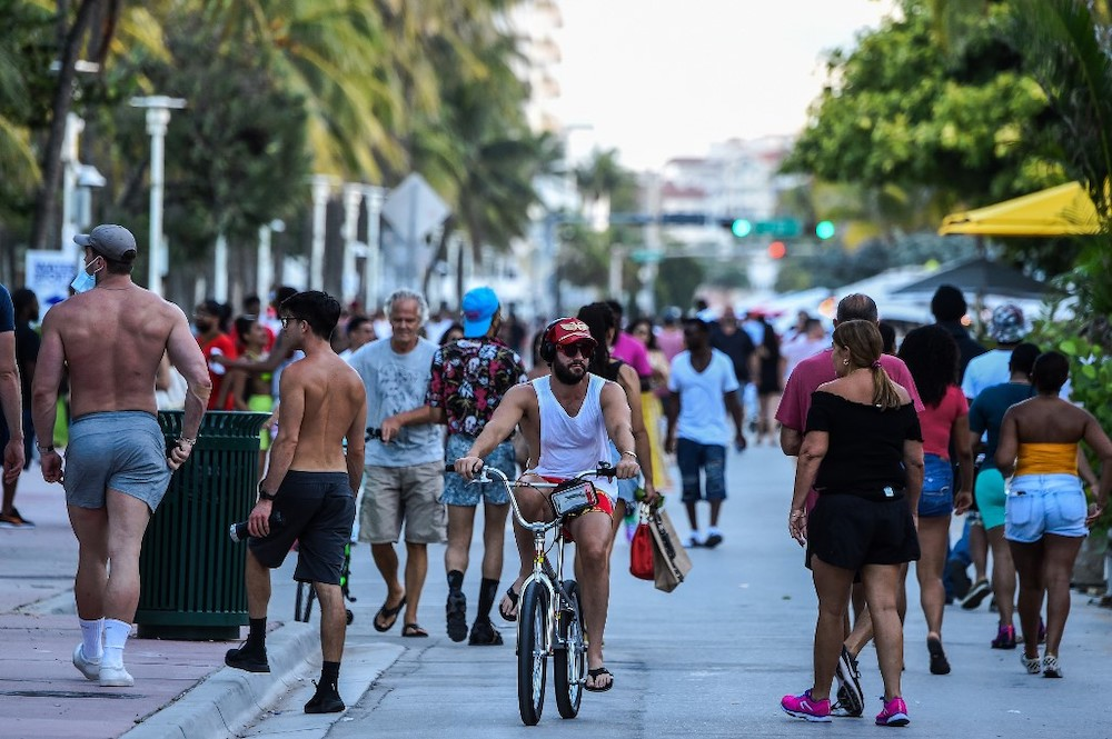 A man rides a bicycle as people walk on Ocean Drive in Miami Beach, Florida on June 26, 2020. — AFP pic