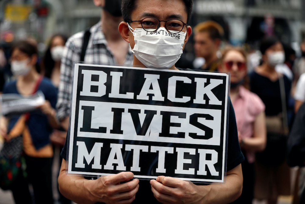 A demonstrator wearing a mask holds a placard during a Black Lives Matter protest, at Shibuya shopping and amusement district in Tokyo, Japan, June 6, 2020. — Reuters pic