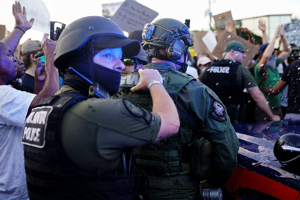 Police escort a police SUV from a crowd of protesters while bottles of water are thrown at them during a rally against the police shooting death of Rayshard Brooks, in Atlanta, Georgia June 13, 2020. — Reuters pic