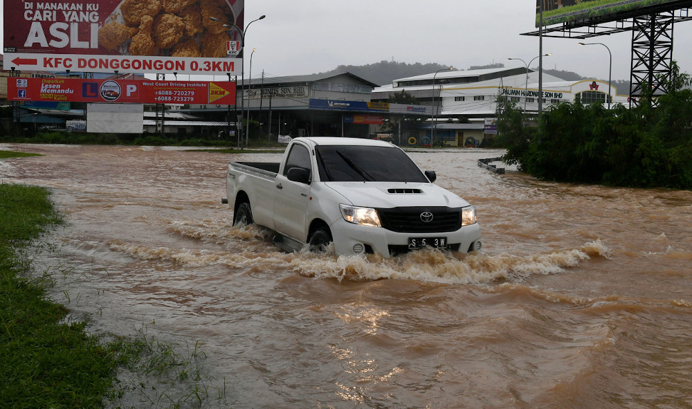 A vehicle is seen stuck in the flood near Donggongon June 27, 2020. — Bernama pic