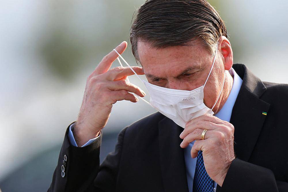 Brazil's President Jair Bolsonaro adjusts his mask as he arrives to a national flag hoisting ceremony in front the Alvorada Palace in Brasilia, Brazil June 9, 2020. — Reuters pic