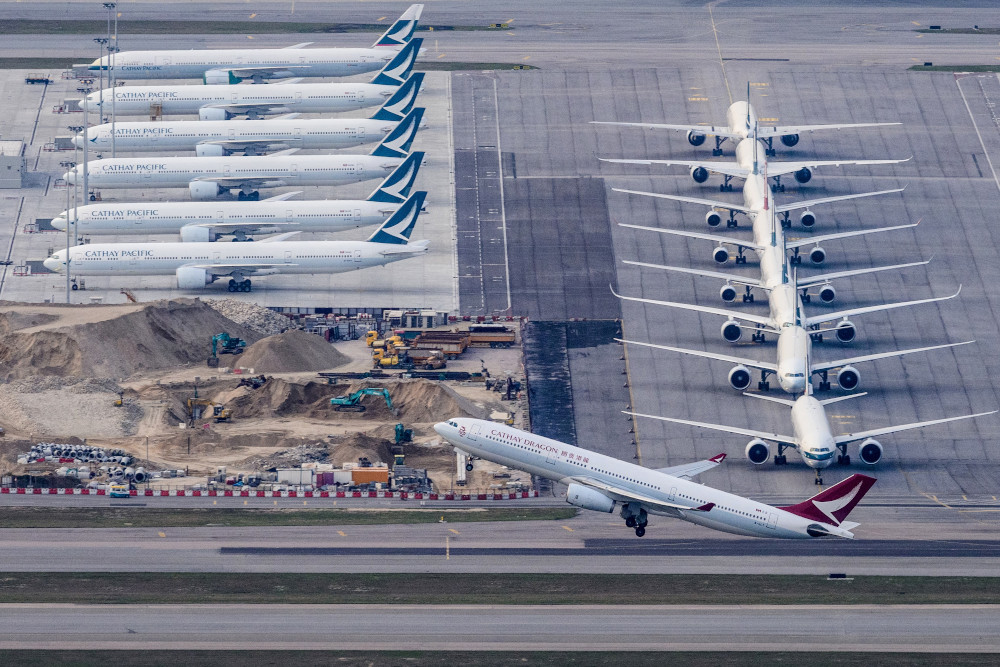 A Cathay Dragon passenger airplane takes off as Cathay Pacific aircraft are seen parked on the tarmac at Hong Kong's Chek Lap Kok International Airport March 10, 2020. — AFP pic
