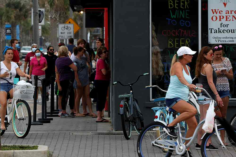 People stand in line at a Duval County restaurant by the beach after it was opened amid Covid-19 restrictions in Jacksonville, Florida April 19, 2020. — Reuters pic