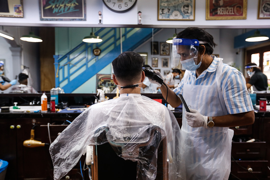 A barber gives his customer a haircut on the first day of the recovery movement control order at the Son And Dad Barber Shop in George Town June 10, 2020. — Picture by Sayuti Zainudin