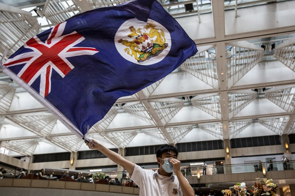 A pro-democracy protester waves a British colonial flag during a 'Lunch With You' rally in a shopping mall in the Central district in Hong Kong on June 1, 2020. — AFP pic