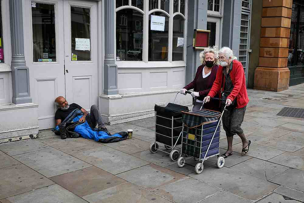 Women wearing face masks and pushing shopping bags on wheels walk past a homeless man a day before all shops were permitted to re open as the Covid-19 lockdown eases in London, Britain June 14, 2020. — Reuters pic