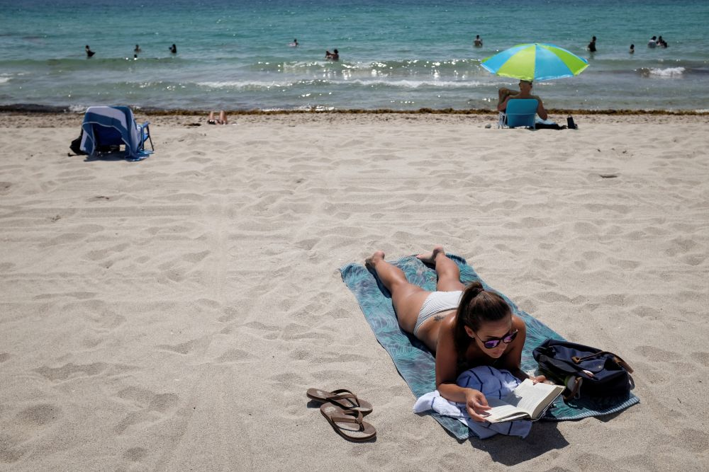 A woman sunbathes while reading a book as beaches are reopened with restrictions to limit the spread of the coronavirus disease in Miami Beach, Florida June 10, 2020. — Reuters pic