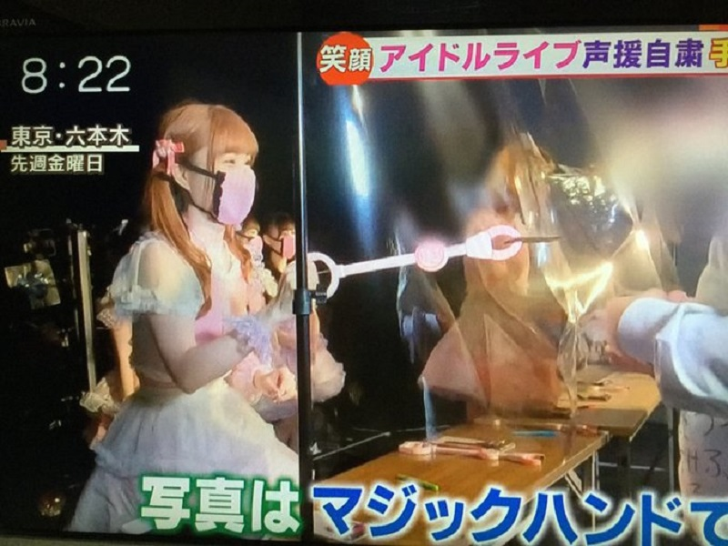 A member from the musical group Momoiro Revolution hands a photograph to a fan using a claw grabber. ― Picture via Twitter/@nagaokakyou_001