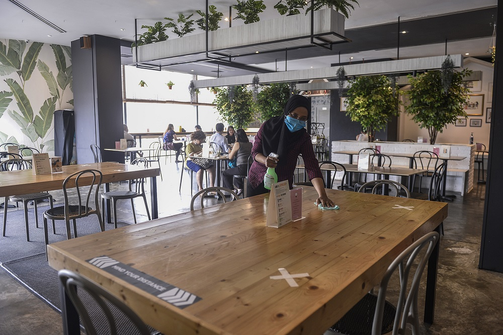 A worker sanitises a table at the Marmalade Cafe in Bangsar Village June 20, 2020. ― Picture by Miera Zulyana