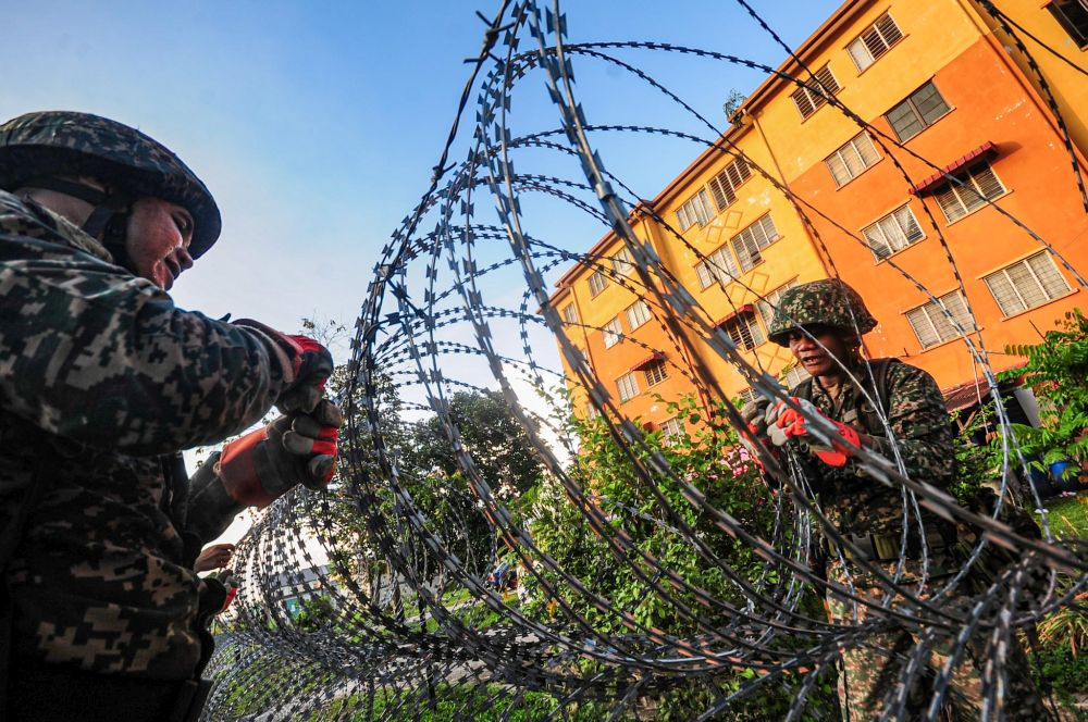 Armed Forces personnel erect barbed wire fencing next to a residential building in Taman Langat Utama June 3, 2020. — Picture by Hari Anggara