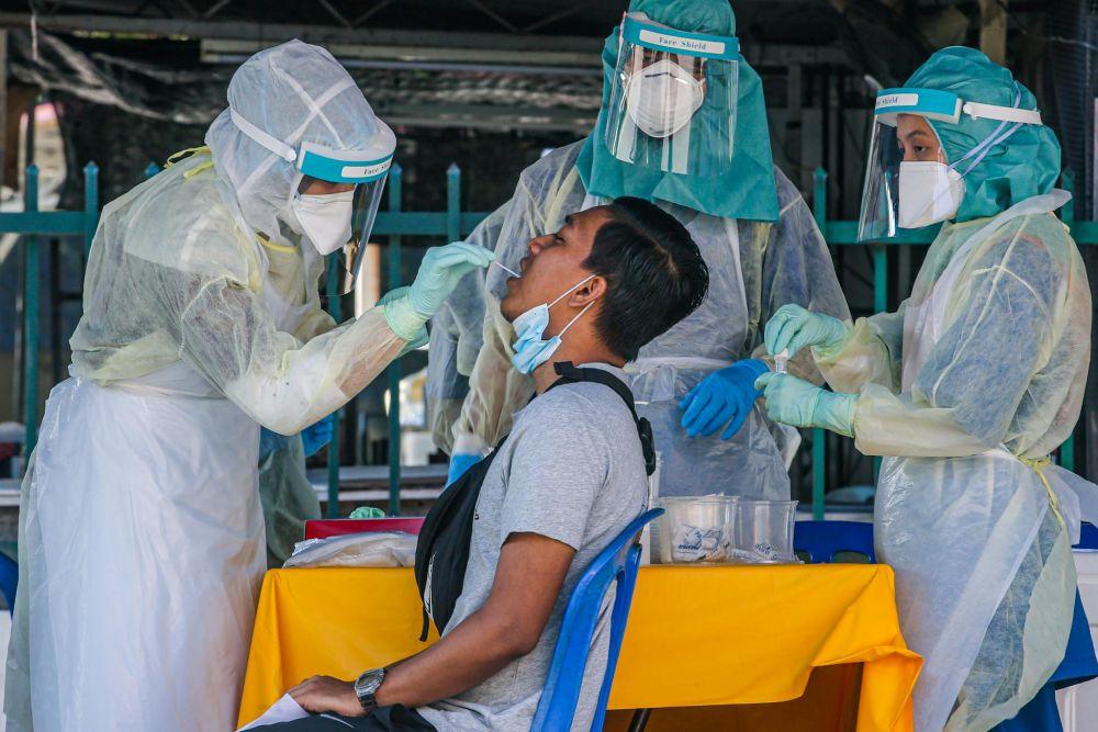 A man undergoes a swab test during a Covid-19 screening exercise in Taman Langat Utama June 3, 2020. — Picture by Hari Anggara