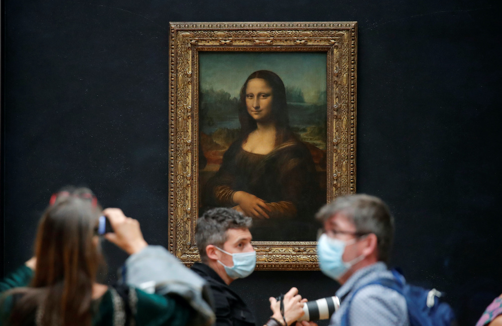 Media people, wearing protective face masks, stand in front of the painting 'Mona Lisa' (La Joconde) by Leonardo Da Vinci at the Louvre museum in Paris as the museum prepares to reopen its doors to the public, June 23, 2020. — Reuters pic
