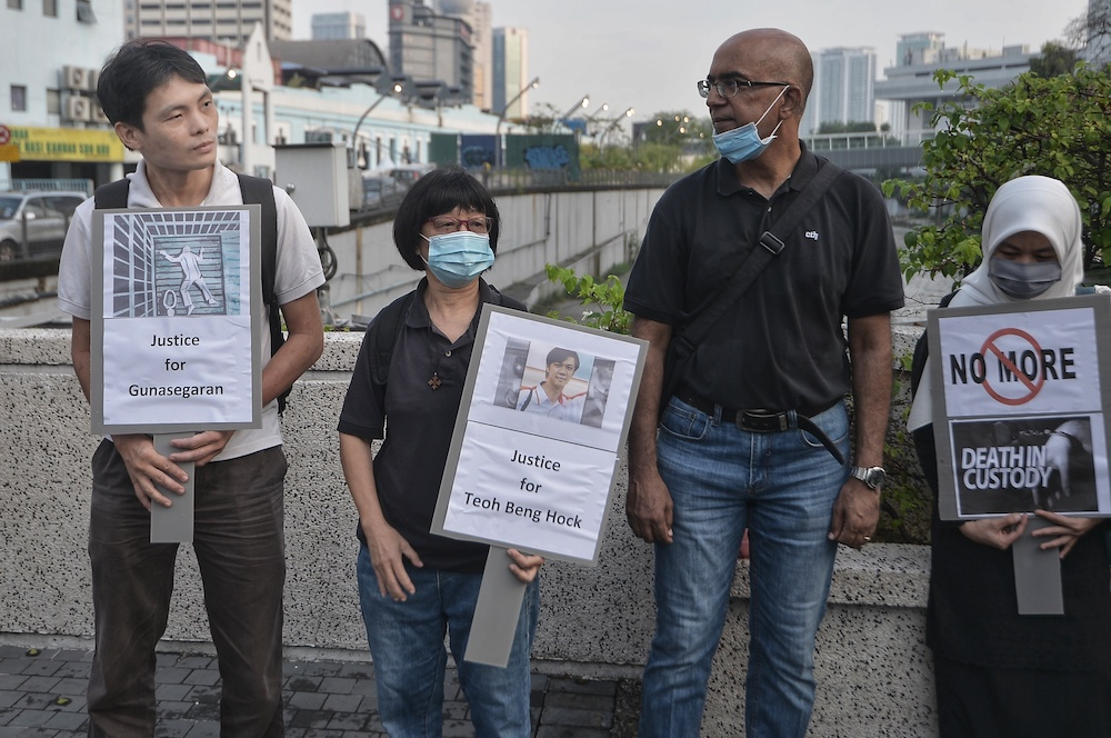 People hold placards during the Malaysia's Custodial Death Black Thursday organised by Eliminating Death & Abuse In Custody Together at the Klang River in Kuala Lumpur July 16, 2020. — Picture by Shafwan Zaidon