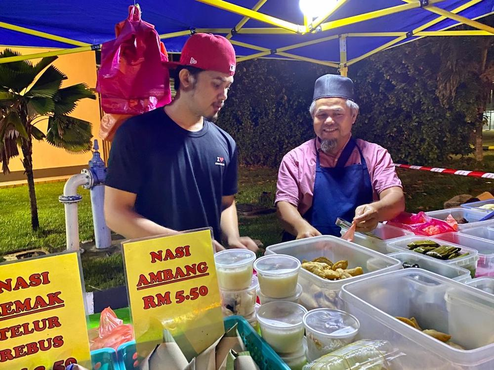 Jasri Amir (right), who has a makeshift food outlet in Taman Perling, has seen his earnings fall by more than half. — Picture by Ben Tan