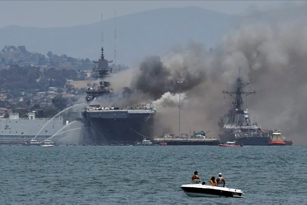 Firefighting boats spray water onto the US Navy amphibious assault ship USS Bonhomme Richard as smoke rises from a fire on board the ship at Naval Base San Diego, as seen from Coronado, California July 12, 2020. — Reuters pic