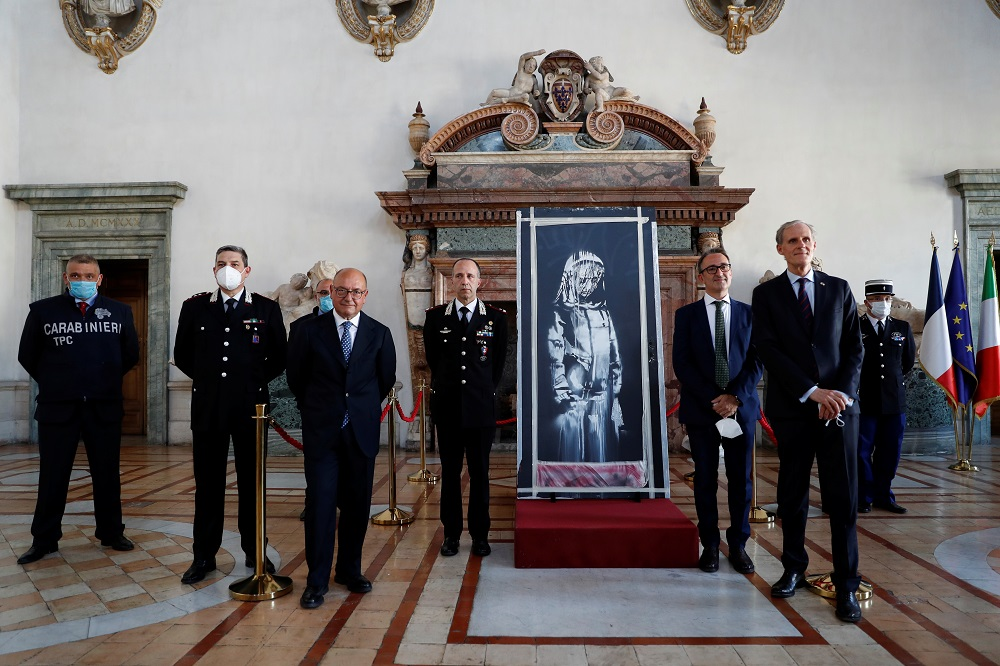 A mural by anonymous British street artist Banksy stolen from the Bataclan theatre in Paris and found in a farmhouse in central Italy is seen during the ceremony to return to France at the French embassy in Rome, Italy. July 14, 2020. — Reuters pic