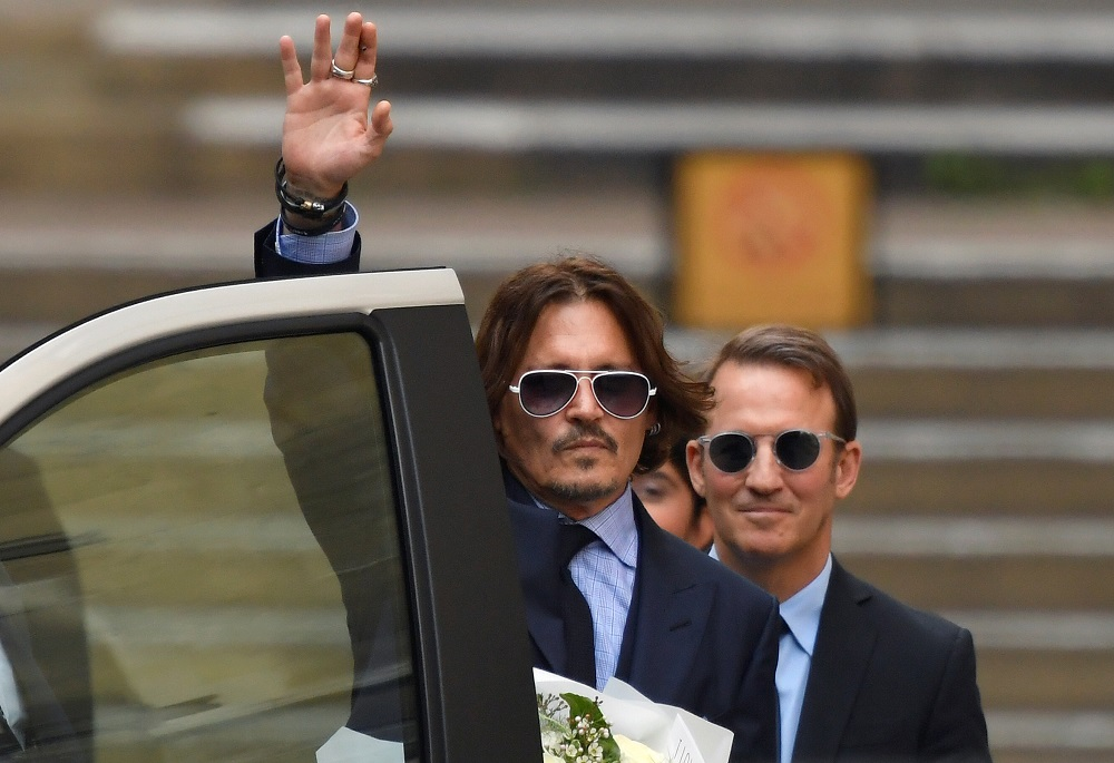 Actor Johnny Depp waves as he leaves the High Court in London July 14, 2020. — Reuters pic