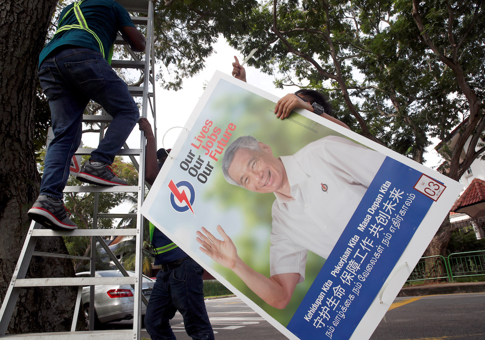 Workers hang up electoral poster for ruling People's Action Party ahead of the general election in Singapore June 30, 2020. — Reuters pic
