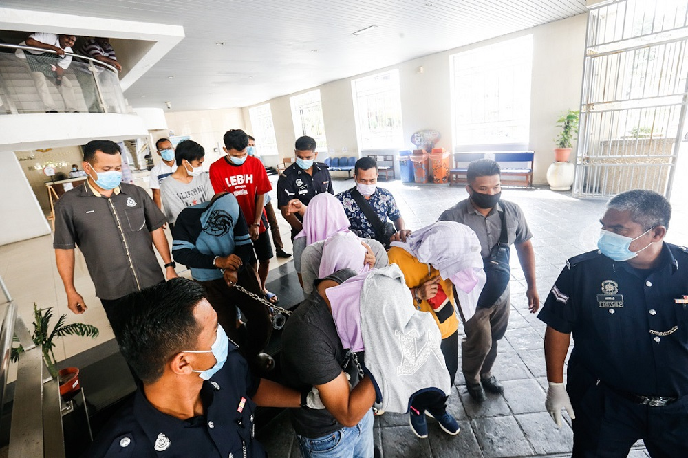 Seven men, including three policemen and two foreigners, are escorted to the lock-up after facing charges of armed robbery at the George Town Sessions Court July 24, 2020. — Picture by Sayuti Zainudin