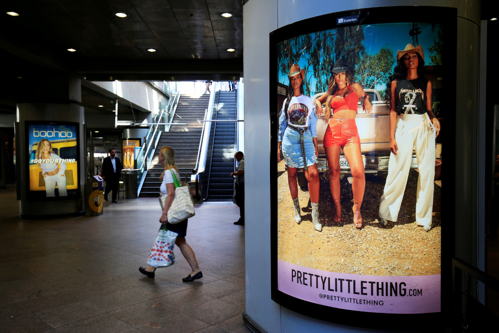 A shopper walks pass advertising billboards for Boohoo and for 'Pretty Little Things', a Boohoo brand, at Canary Wharf DLR station in central London, Britain, September 17, 2018. — Reuters pic