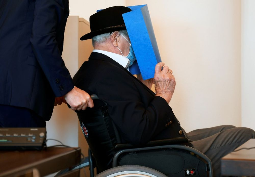 Bruno Dey, a former SS-watchman at the Stutthof concentration camp, hides his face behind a folder as he arrives on a wheelchair for a hearing in his trial on July 23, 2020 in Hamburg, northern Germany. — AFP pic