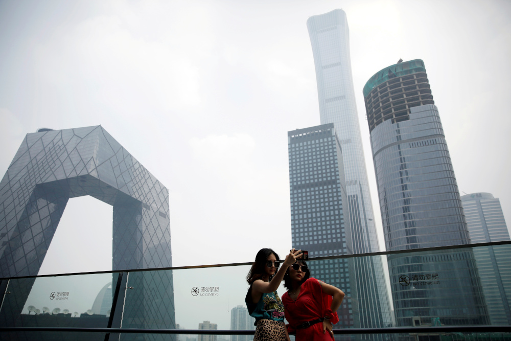 Women pose for pictures at a shopping mall near the CCTV headquarters and China Zun skyscraper in Beijing's central business district (CBD), China, July 16, 2020. — Reuters pic