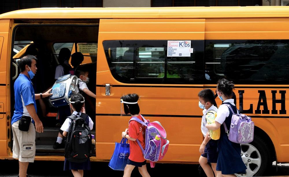 School children are seen getting on a school bus outside SJK Shang Wu in George Town July 22, 2020. — Bernama pic
