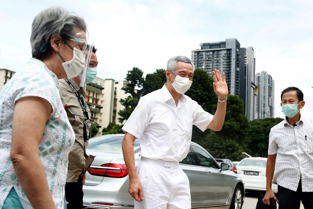 Singapore's Prime Minister Lee Hsien Loong and his wife Ho Ching at a polling station during Singapore's general election, amid the coronavirus disease outbreak, in Singapore July 10, 2020. — AFP pic