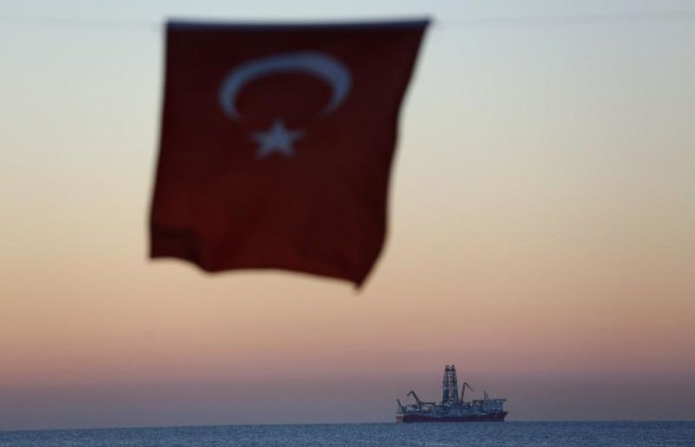 The Turkish national flag hangs in the foreground as drilling vessel Fatih is seen off the Mediterranean resort city of Antalya, Turkey October 30, 2018. — Reuters pic