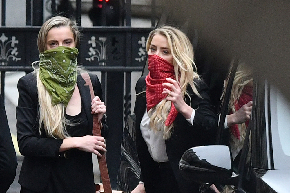 US actress Amber Heard (right) arrives on the third day of the libel trial by her former husband US actor Johnny Depp against News Group Newspapers (NGN), at the High Court in London, July 9, 2020. — AFP pic