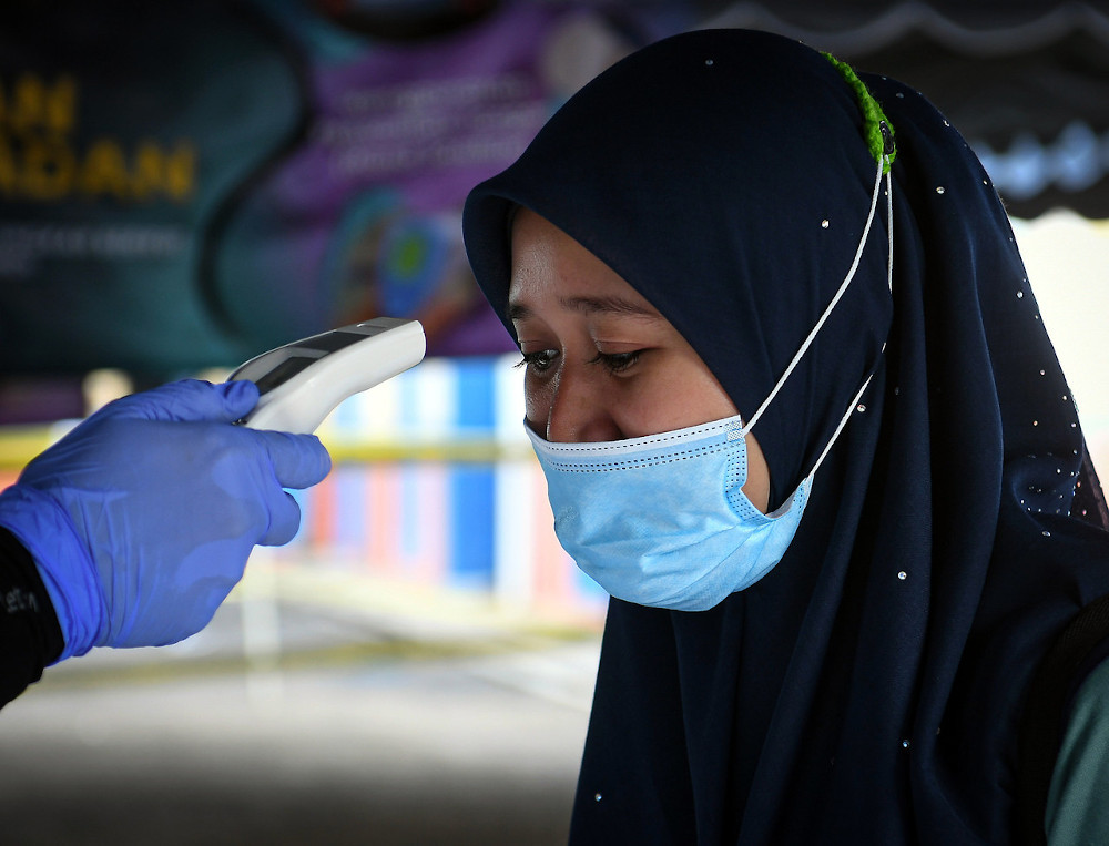 An official takes the temperature of a voter outside the voting centre for the Chini by-election July 4, 2020. — Bernama pic
