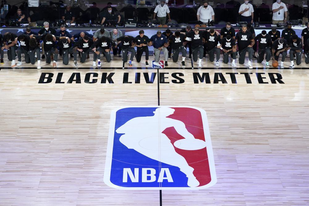 Members of the New Orleans Pelicans and Utah Jazz kneel together around the Black Lives Matter logo on the court during the national anthem before the start of an NBA basketball game July 30, 2020. — Reuters pic