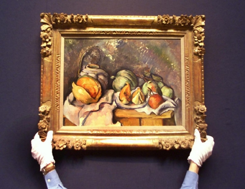 A Christie's employee holds up Cezanne's 'Nature morte aux fruits et pot de gingembre' (Still life with fruits and ginger pot) at the press preview for the latest Impressionist auction at Christie's in London 23 June 2000. ―AFP pic